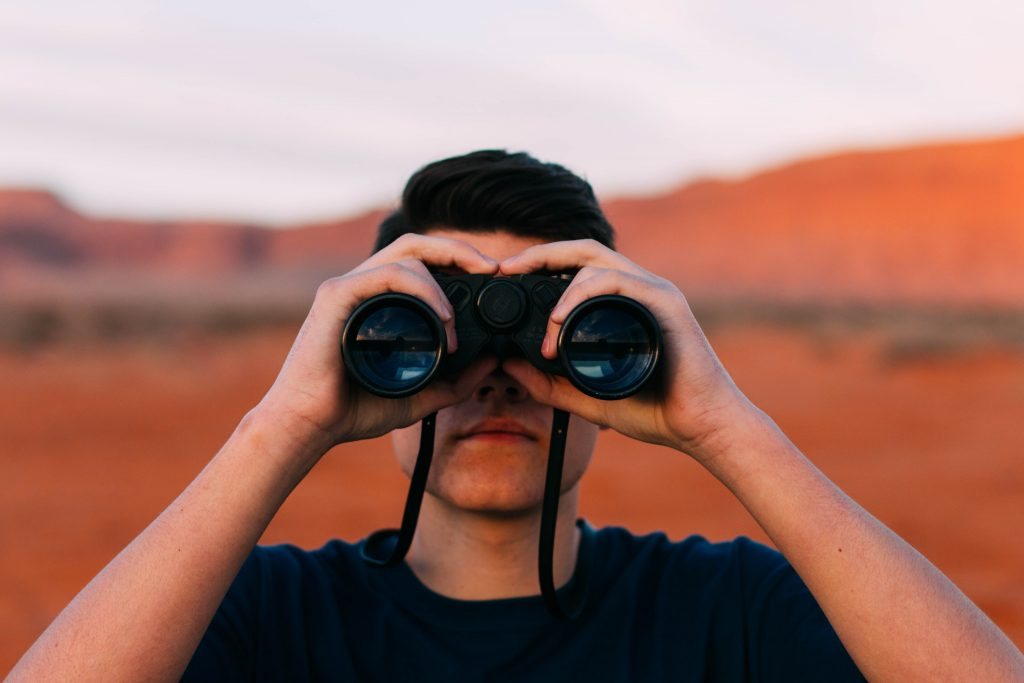 Man looking for remote work with binoculars